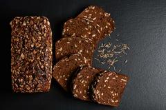 构成黑暗的黑麦,与向日葵种子的谷物面包, Wonder面包,小茴香五谷在黑暗的背景页岩的上,概念  免版税图库摄影