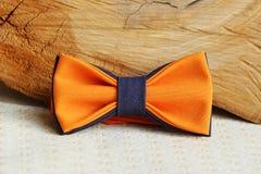 构成:与一个灰色蝶形领结的桔子和在米黄背景的木棍子 免版税库存图片