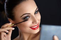 构成 做构成的美丽的妇女 染睫毛油刷子 红色的嘴唇 免版税库存照片