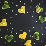 构筑与柑橘和猕猴桃的心脏的背景在黑背景 食物框架 平的位置,顶视图 库存图片