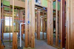 构筑小马墙壁和新的木盆和新的塑料配管的用管道输送连接到老铜管子 库存图片
