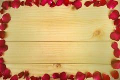 构筑形状由玫瑰花瓣做成在木背景, Valentin 免版税库存图片