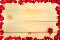 构筑形状由玫瑰花瓣做成在木背景, Valentin 免版税库存照片