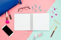 构筑flatlay与妇女` s蓝色袋子、玻璃、智能手机有黑copyspace的,化妆用品、固定式供应和笔记本有b的 免版税库存照片