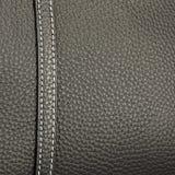 构造与整洁的针的黑皮革缝合与白色螺纹 免版税库存照片