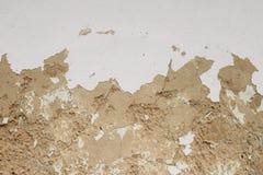 构造在黄色老黏土墙壁上的被用完的白色白涂料 库存图片