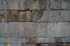 构造被风化的老自然石砖墙背景在浅灰色的与联合和毛面 免版税图库摄影