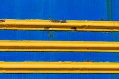 构造金属表面,被绘的蓝色,与水平的黄线 免版税库存图片