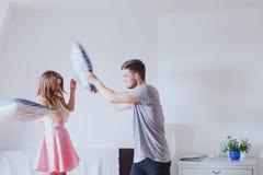 枕头战,获得年轻愉快的家庭的夫妇乐趣在家 免版税库存图片