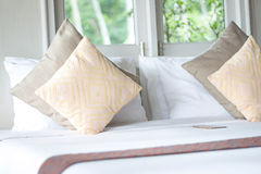 枕头,由窗口的床在卧室 图库摄影