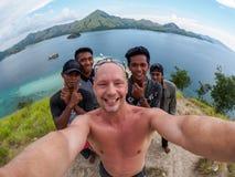 林卡岛,印度尼西亚- 2018年4月01日:白种人人在林卡岛海岛附近做与当地人民的Selfie 库存图片