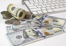 100枚美元钞票和金钱硬币 使用keyboar的计算机 免版税库存图片