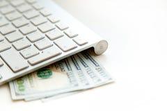 100枚美元钞票和金钱硬币 使用keyboar的计算机 图库摄影