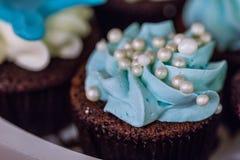 果仁巧克力与蓝色被鞭打的奶油色转动和白色珍珠的杯形蛋糕松饼成串珠状顶部 免版税库存照片