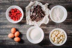 果仁巧克力或巧克力蛋糕松饼的烘烤成份用在木背景的樱桃 免版税库存图片