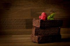 果仁巧克力,可口被堆积的果仁巧克力用在木背景隔绝的莓, 图库摄影