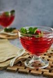 果冻用在一块玻璃的草莓在一个木板,反对混凝土背景  免版税库存照片