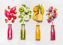 水果和蔬菜圆滑的人的分类在玻璃瓶的有在白色木背景的秸杆的 免版税库存照片