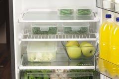 水果和蔬菜在两个容器在一个现代冰箱 库存照片