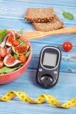 水果和蔬菜沙拉和glucometer与糖尿病的卷尺,概念,减肥和健康营养 免版税图库摄影