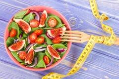 水果和蔬菜沙拉,与卷尺,减肥和营养概念的叉子 免版税库存照片
