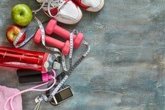 果子、哑铃、一个瓶水,绳索、运动鞋和米在蓝色有离婚背景 库存图片