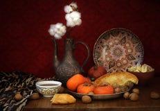 果子、坚果、平的蛋糕、水罐和东方甜点在桌上 免版税库存图片