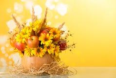 果子、花和刺的原始的构成在南瓜在席子由西沙尔麻制成在黄色 免版税库存图片