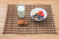 果子、莓果和麦甜饼健康早餐用牛奶在木背景 免版税库存图片