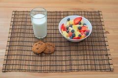果子、莓果和麦甜饼健康早餐用牛奶在木背景 免版税图库摄影
