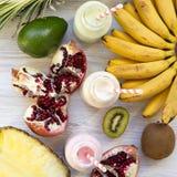 果子不同的口味圆滑的人或奶昔在玻璃瓶的有白色木表面,顶视图上的成份的 r 免版税库存照片