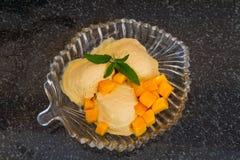 果子与新鲜水果切片的冰淇凌与叶子在一块玻璃板铸造 免版税库存图片
