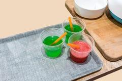 果子与秸杆的饮料样品在小品尝的杯子 免版税库存照片