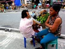 果子供营商卖绿色芒果的和棉花结果实在边路 库存图片