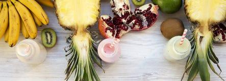 果子各种各样的口味圆滑的人或奶昔在玻璃瓶的有在白色木背景,顶视图的成份的 从上 库存照片