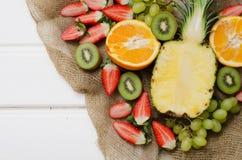 果子和莓果在白色木头 免版税库存照片
