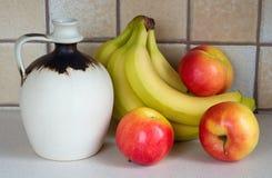 果子和陶瓷水罐 免版税库存照片