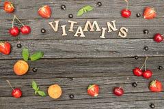 果子和题字维生素在黑木背景,食物概念 复制空间 图库摄影