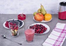 果子圆滑的人用蓝莓、莓、苹果、桔子、梨和香蕉在灰色背景 免版税库存照片