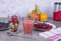 果子圆滑的人用蓝莓、莓、苹果、桔子、梨和香蕉在灰色背景 免版税图库摄影