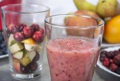 果子圆滑的人用蓝莓、莓、苹果、桔子、梨和香蕉在灰色背景 库存照片
