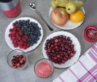 果子圆滑的人用蓝莓、莓、苹果、桔子、梨和香蕉在灰色背景 库存图片