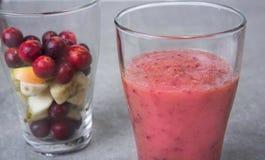 果子圆滑的人用蓝莓、莓、苹果、桔子、梨和香蕉在灰色背景 免版税库存图片
