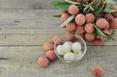 果子在碗和新鲜的lychee剥了皮在木桌上 免版税图库摄影