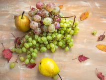 果子套绿色和多彩多姿的葡萄,在木背景的梨,秋叶 免版税库存图片
