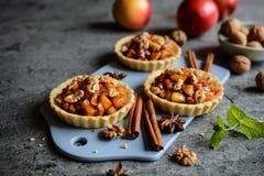 果子果子馅饼用焦糖的苹果片、桂香和核桃填装了 库存图片