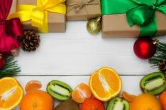 果子桔子、猕猴桃和礼物盒有丝带弓的和红色球在白色木减速火箭的背景 免版税库存照片