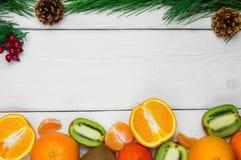 果子桔子、蜜桔和分支在白色木土气背景的圣诞树锥体 免版税库存照片