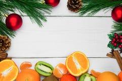 果子桔子、蜜桔和猕猴桃 分支圣诞树和红色球与锥体和肉桂条在白色木葡萄酒ba 库存图片