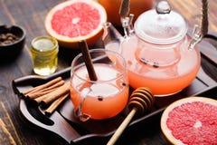 果子清凉茶用香料和蜂蜜在玻璃茶壶和杯子黑暗的木背景中 图库摄影
